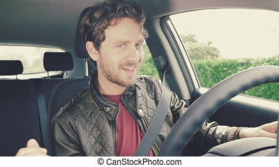 Handsome man looking camera smiling happy driving car slow motion retro