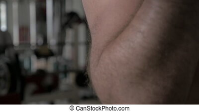 Strong man working out with dumb-bell - Close-up shot of a...
