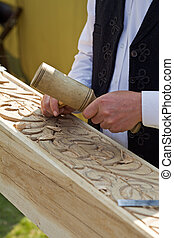 Traditional craftsman carving wood with floral motifs