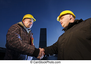 handshake - Two applied to construction workers wearing...