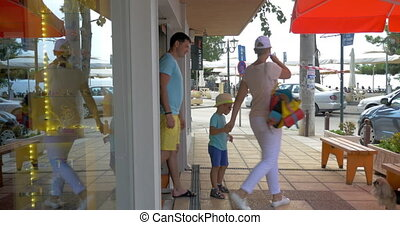Family of three leaving store and walking in the street