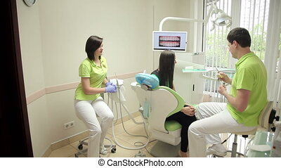 dentist talking to a patient in medical office - dentist...