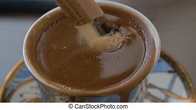 Putting brown sugar into coffee - Close-up shot of adding...