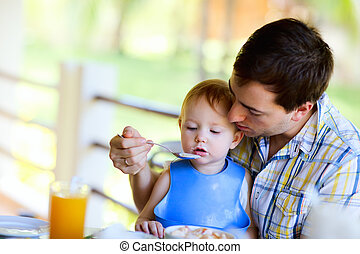 Young  father and his daughter having breakfast together