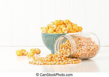 Popcorn Kernels - Jar of uncooked popcorn with a bowl of...