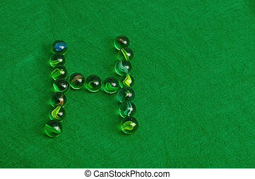 Letter H - The letter H made out of marbles on a green...
