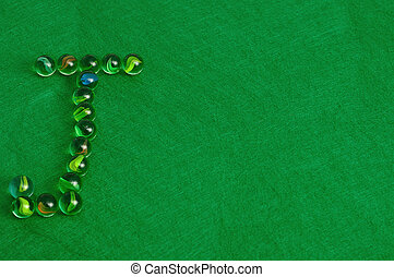 Letter J - The letter J made out of marbles on a green...