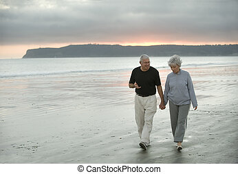 Senior Couple on the Beach - Senior husband and wife walking...