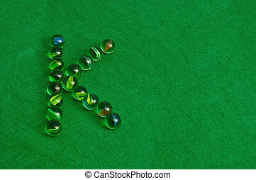 Letter K - The letter K made out of marbles on a green...