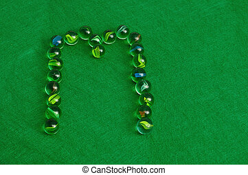 Letter M - The letter M made out of marbles on a green...