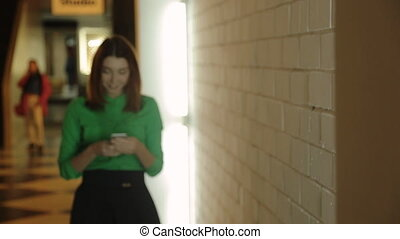The young woman is going in the hall with the cellphone in her hands texting, typing or dialing the number.