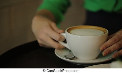 The woman sitting at the table is moving the cup of coffee up and down drinking the cappuccino