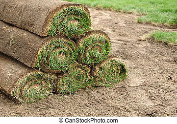 Stack of Sod Rolls - A Stack of Sod Rolls on the Dirt