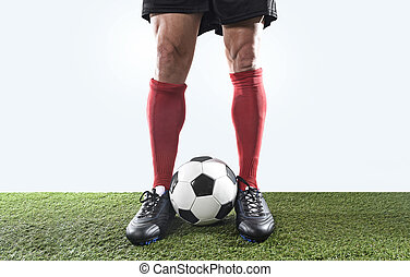 legs feet of football player in red socks and black shoes posing with the ball playing on green grass pitch