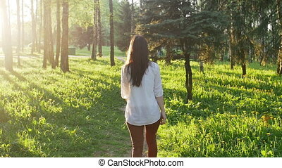 Woman walking in the forest at sunset. Slow motion - Young...
