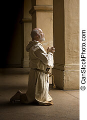 Monk in Prayer - Barefood monk praying on his knees in a...