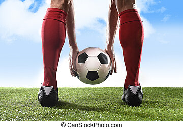 football player in red socks and black shoes holding ball in his hands placing free kick or penalty