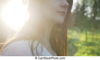 woman in the rays of the setting sun in the forest -...