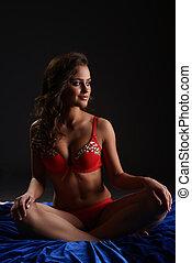 Seductive brunette in underwear sitting on bed