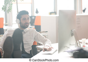 relaxed young business man at office - happy young arabian...