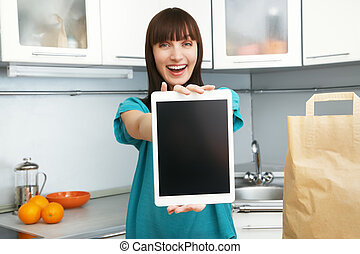 housewife uses a tablet computer in the kitchen - selective...