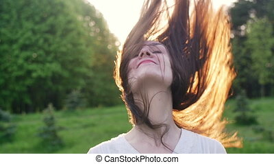 Happy woman raises her head and hair. slow motion