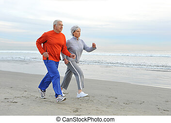 Jogging Seniors - Senior couple jogging on the beach in the...