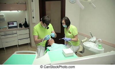 Dentist and assistant treating the patient teeth - Doctor...