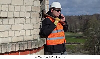 Construction worker with sledgehammer talking on tablet PC