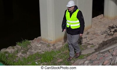 Engineer checking documentation near bridge construction