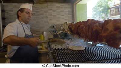 Cook in cafe grilling bread and roasting meat - Male cook in...