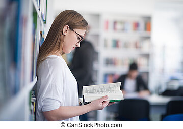 portrait of famale student reading book in library -...