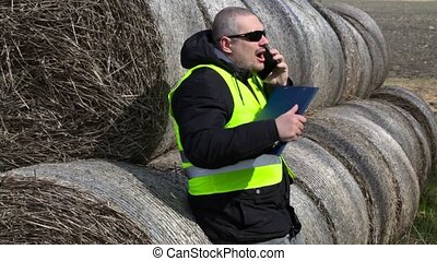 Farmer talking on smartphone near the hay bales