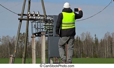 Engineer take pictures on tablet PC near power transformer
