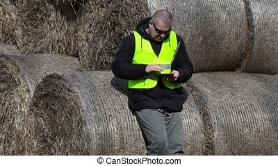 Farmer using tablet PC near the hay bales
