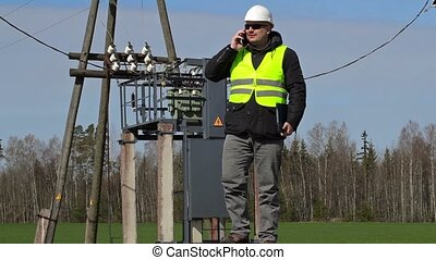 Engineer talking on smartphone near power transformer