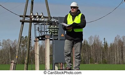 Engineer with folder near power transformer