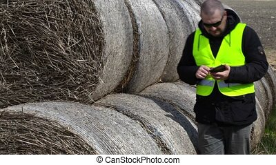 Farmer walking and using tablet PC near the hay bales