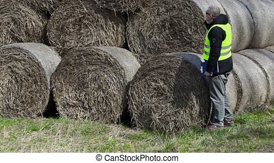 Farmer checking hay bales and talking on smartphone