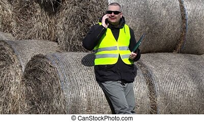 Farmer with smartphone talking near the hay bales