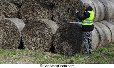 Farmer with tablet PC numbering the hay bales