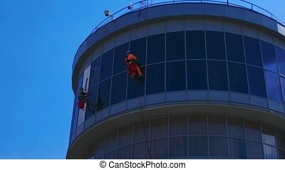 Window Washers on a Office Building Industrial climbers Make...