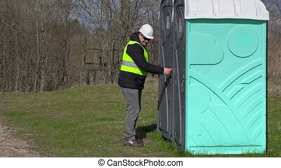 Worker waiting near portable toilet