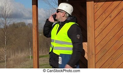 Civil engineer talking on smart phone at the wooden...