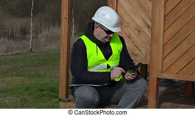 Civil engineer using tablet PC at the wooden structure of...