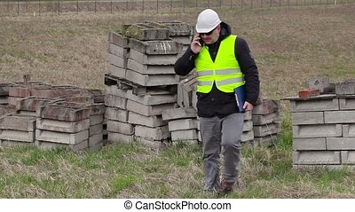 Civil engineer with smart phone at place where will new...