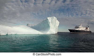 A large iceberg and the ship in the Arctic.