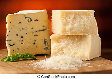 pieces of blue cheese and parmesan on a wooden cutting board...