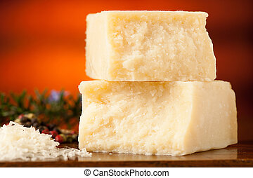 pieces of parmesan cheese on a wooden cutting board being...