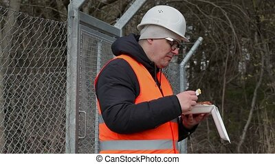 Worker with food near wire fence